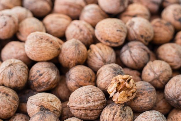 Walnut kernels on natural walnut background, raw bio walnuts texture, top view