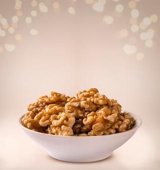 Walnut kernels in white bowl on beige background.