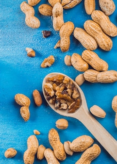 Грецкий орех; арахис и фисташки на синем текстурированном фоне