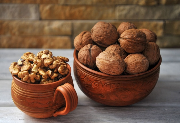 Walnut peeled and inshell in pottery on a white wooden table.