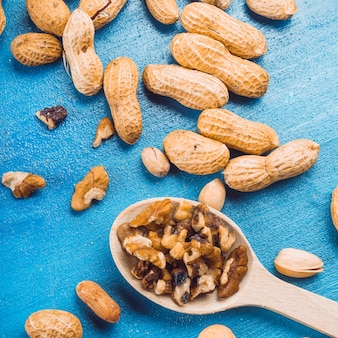 Walnut pieces on wooden spoon with peanuts and pistachio on blue background