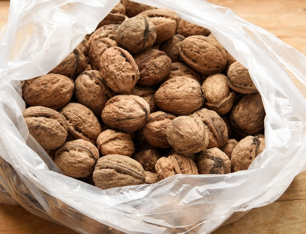 Walnut in a plastic bag on a wooden table, top view