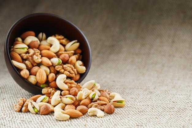 Ореховое блюдо вылилось из чашки на фоне ткани из мешковины