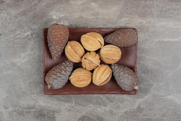 호두 모양의 쿠키와 어두운 접시에 pinecones. 고품질 사진