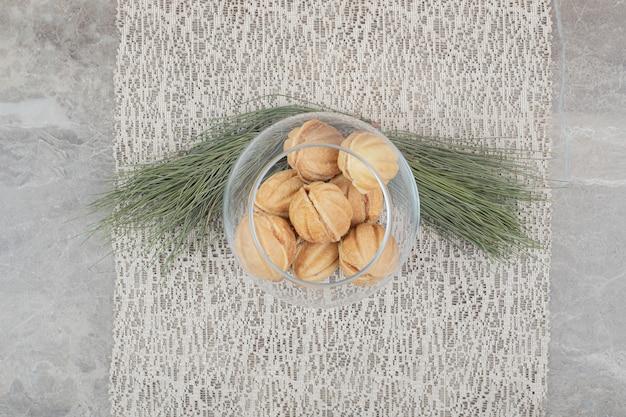 Biscotti a forma di noce in ciotola di vetro su tela da imballaggio. foto di alta qualità