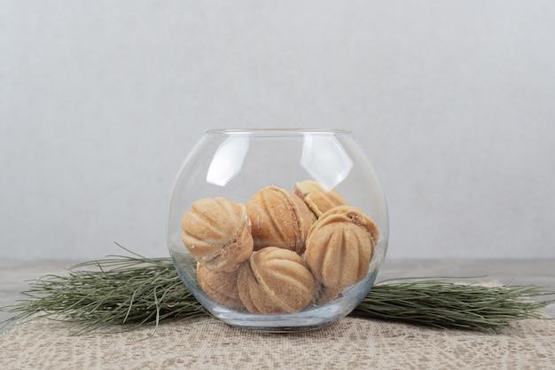 Biscotti a forma di noce in ciotola di vetro su tela da imballaggio.
