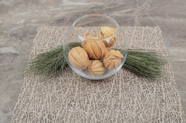 Walnut shaped cookies in glass bowl on burlap.