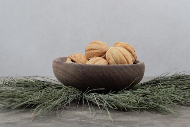 Печенье в форме грецкого ореха в деревянной миске.