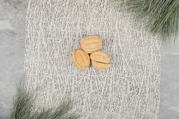 枝のある黄麻布にくるみの形をしたクッキー。高品質の写真