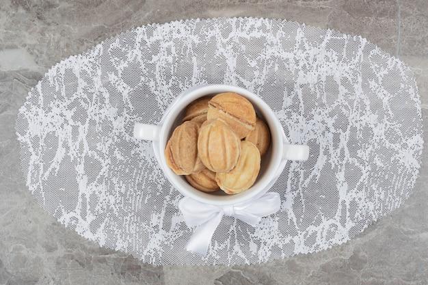 Biscotti a forma di noce in ciotola bianca con nastro. foto di alta qualità