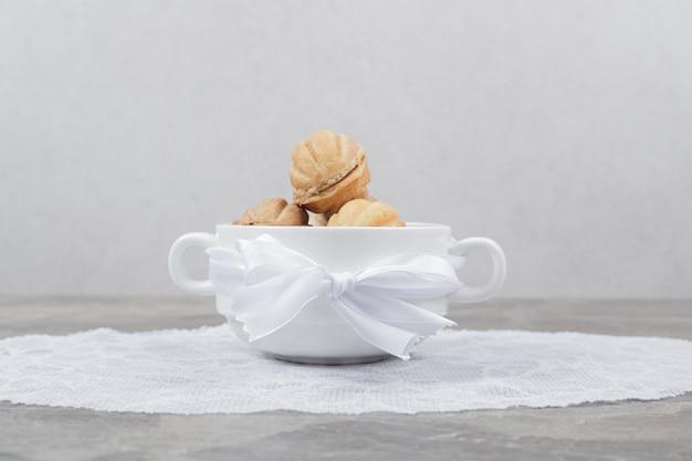 Biscotti a forma di noce in ciotola bianca.