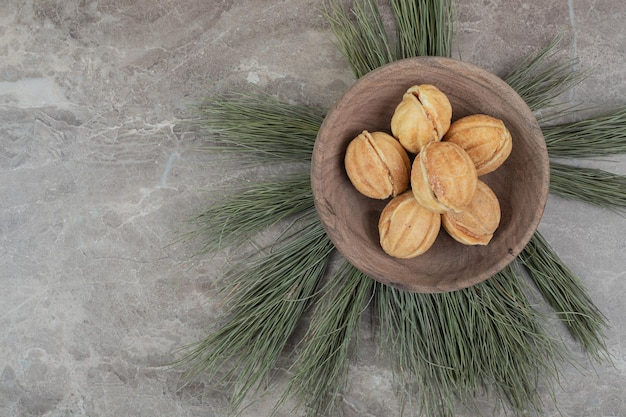 Walnut shaped cookies in wooden bowl.