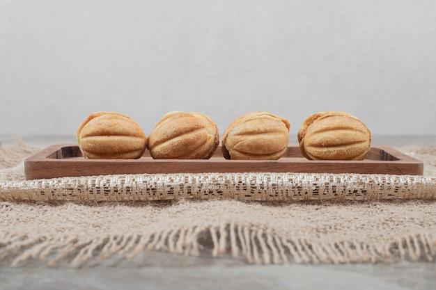 Biscotti a forma di noce sul piatto di legno.