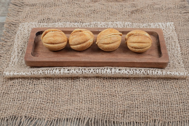 Walnut shaped on wooden plate with burlap.
