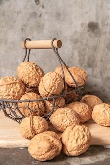 Walnut in steel basket on the cement table.