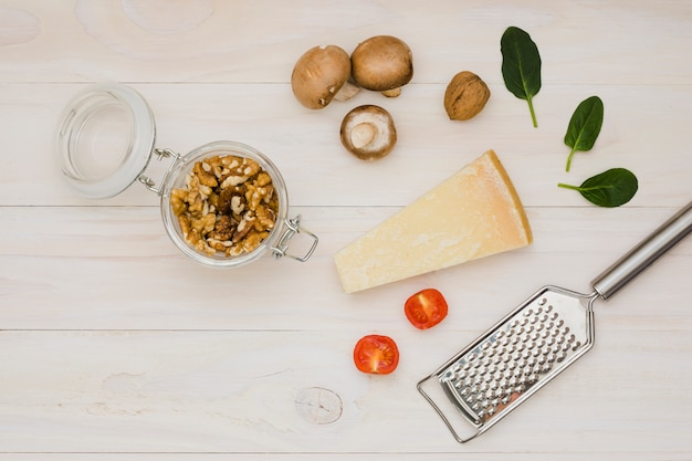 Walnut; tomatoes; cheese; basil and mushroom with metal grater on wooden desk