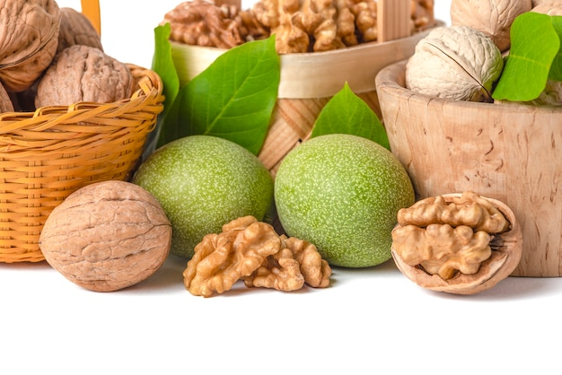 Walnut. walnut fruits of different varieties lie in wooden saucers and baskets on a white isolated background. nearby are green leaves and unripe walnut fruits.
