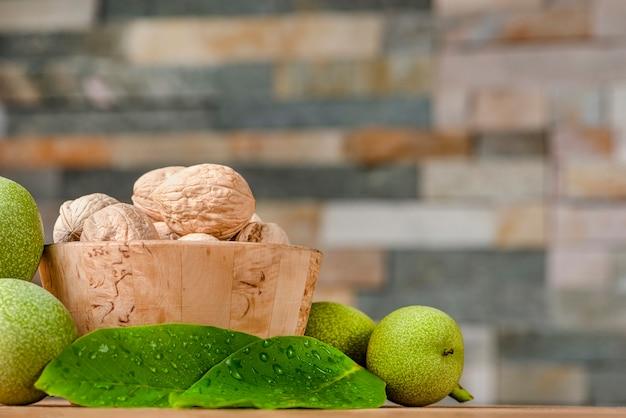 호두. 호두 과일은 나무 접시에 놓여 있습니다. 근처에는 녹색 잎과 덜 익은 호두 열매가 있습니다. 배너, 공간 복사 또는 텍스트 붙여넣기.