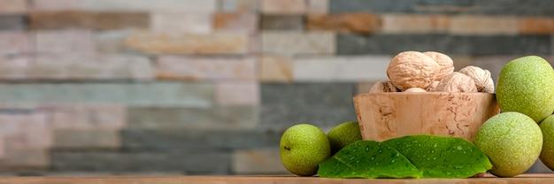 호두 과일은 근처의 나무 접시에 놓여 있으며 녹색 잎과 설익은 호두 과일 배너입니다...
