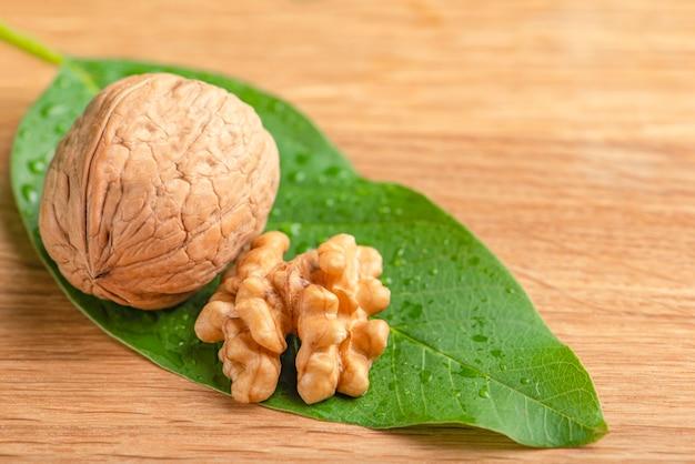 Плоды грецкого ореха лежат на зеленых листьях с каплями воды зеленые листья грецкого ореха на деревянном фоне
