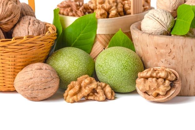 Грецкий орех. плоды грецкого ореха разных сортов лежат в деревянных блюдцах и корзинах на белом изолированном фоне. рядом зеленые листья и незрелые плоды грецкого ореха.