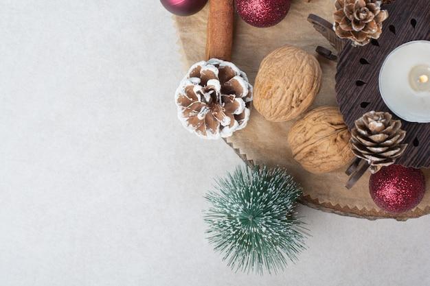 木の板に松ぼっくりとクリスマスボールとクルミ。高品質の写真