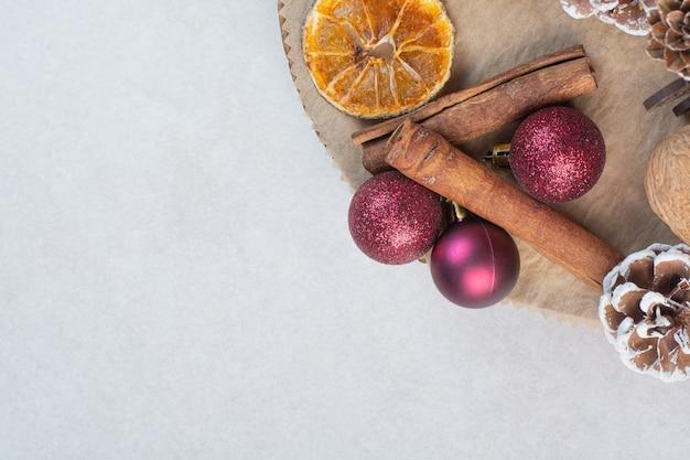 Noce con pigne nelle quali e palle di natale sul piatto di legno. foto di alta qualità