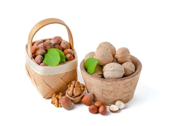 다양한 종류의 호두와 헤이즐넛은 흰색으로 분리된 b에 나무 접시와 바구니에 놓여 있습니다.