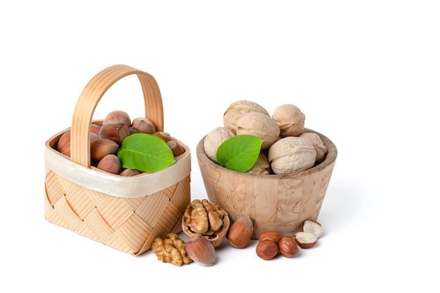 다양한 종류의 호두와 헤이즐넛은 흰색 격리된 배경에 나무 접시와 바구니에 있습니다. 근처에 있는 녹색 잎, 호두 및 껍질을 벗긴 헤이즐넛