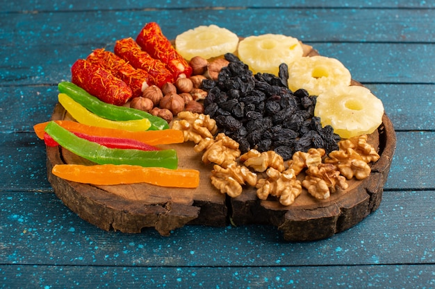 Грецкие орехи и нуга с желе и кольцами ананаса на синем