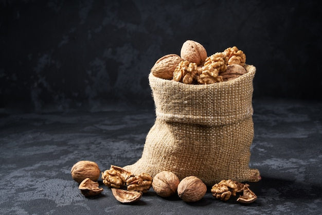 Walnuts  in bag on black table. heap or stack of walnut.
