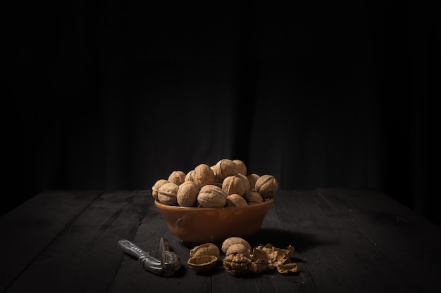 Walnuts in a bowl on dark surface. low-key image of nuts on black rustic table, artistic light and shadow technique and copy space