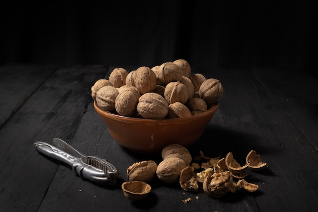 Walnuts in a bowl on dark surface. low-key image of nuts on black rustic table, artistic light and shadow technique