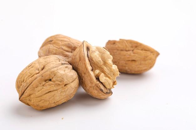 Walnuts and cracked walnut, isolated on white background