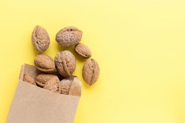 Walnuts in craft paper bag on yellow background. delicious nuts. healthy nutrition. super food. flat lay, top view with copy space.