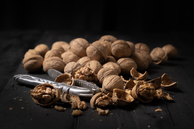 Walnuts on dark surface. low-key image of nuts on black rustic table, artistic light and shadow technique