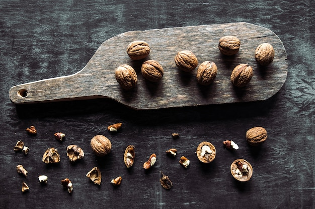 Walnuts on dark vintage table. healthy food. nuts are scattered on a cutting board. old vintage table and leaves from the nut.