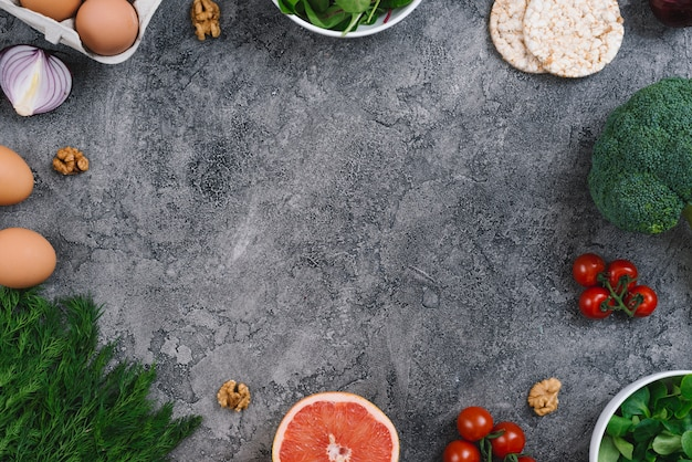 Walnuts and fresh vegetables on concrete gray background