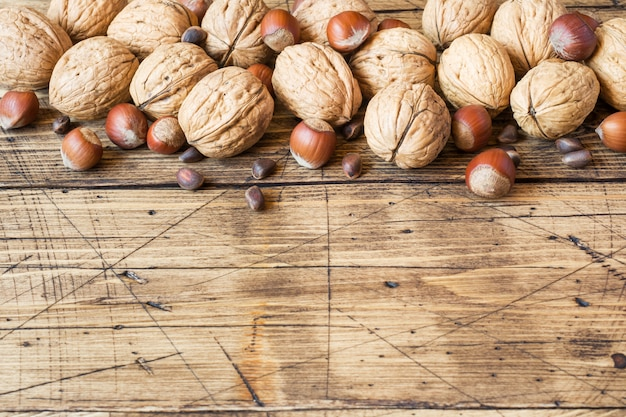 Walnuts, hazelnuts and cedar on a dark surface of old wooden.