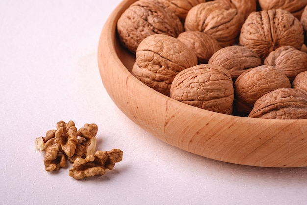 Walnuts heap food in wooden bowl on white background near to peeled nuts, angle view, healthy food concept