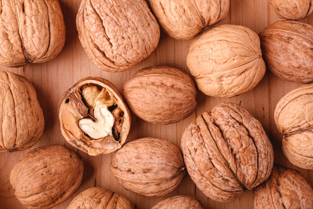 Walnuts heap food in wooden bowl with half peeled nut, top view, healthy food concept