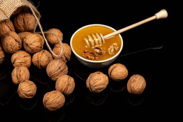 Walnuts and honey in a bag on a black background.