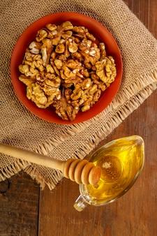 Грецкие орехи в глиняной посуде на мешковине рядом с медом ложкой на деревянном столе вертикальное фото