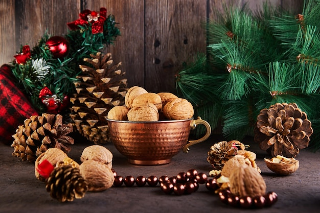 詰め物と殻の隣にある、丸ごと刻んだブリキのカップに入ったクルミ。モミの実で新年の構成で提示