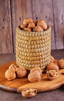 枝編み細工品バスケットに入ったクルミ、丸ごと細かく刻んだもの、木の表面の詰め物と貝殻の横