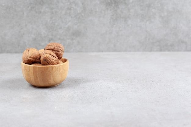 Грецкие орехи в деревянной миске на мраморной предпосылке. фото высокого качества