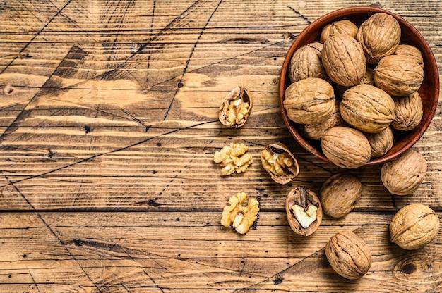 Грецкие орехи в деревянной тарелке и ядра грецких орехов