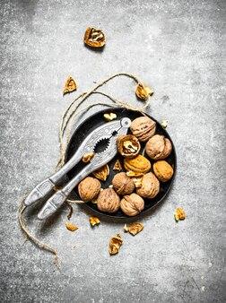 Грецкие орехи в миске с щелкунчиком на каменном столе