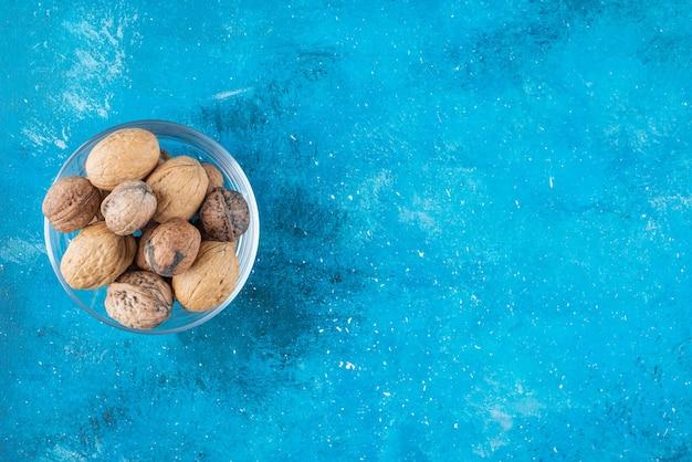 Грецкие орехи в скорлупе в стеклянной миске, на синем столе.