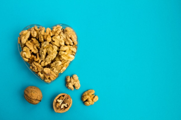 Грецкие орехи в форме сердца на синей поверхности.